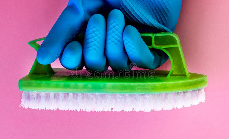 Wiosna czyści, jaskrawi kolory, piękna ręka z błękitną rękawiczką trzyma zielenieje muśnięcie na róży tle, reklamuje zdjęcie stock