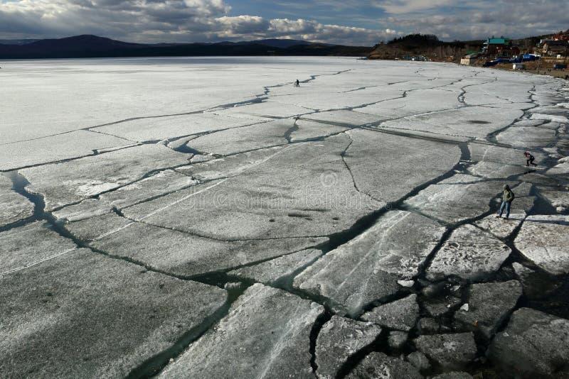 Wiosna krajobraz z lodu dryfem na jeziorze i cykliści jedzie wzdłuż go ludzie i obraz stock