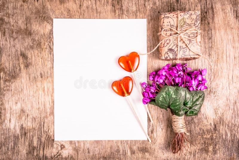 Wiosna kwitnie, romantyczny list, prezenta pudełko Międzynarodowy kobiety ` s dzień Bukiet fiołki lizak w kształcie serca obrazy stock
