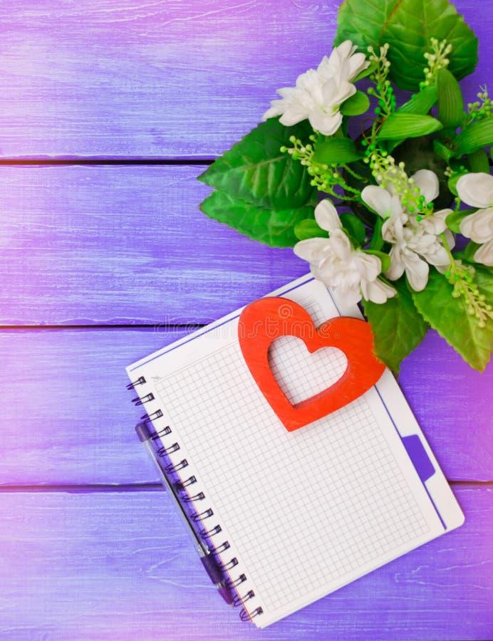 Wiosna, notatnik z piórem, kwiaty, na purpurowym drewnianym backgroun zdjęcia royalty free