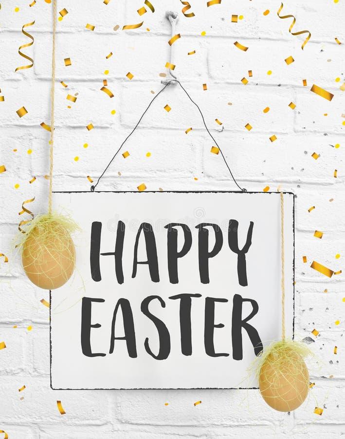 Wiosna przytacza ręcznie pisany tekst szczęśliwy Easter z złotych confetti en realistycznymi dekoracyjnymi jajkami wiesza na  fotografia stock