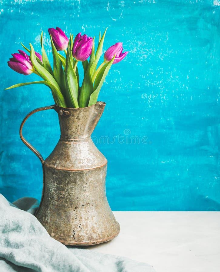 Wiosna purpurowi tulipany w rocznika wieśniaku miedziują dzbanek, błękitny tło zdjęcia stock