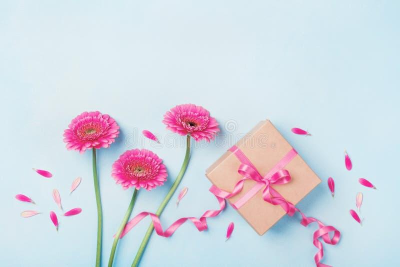 Wiosna skład z menchia kwiatami i prezenta pudełkiem na błękitnym stołowym odgórnym widoku Kartka z pozdrowieniami dla urodziny,  obraz stock