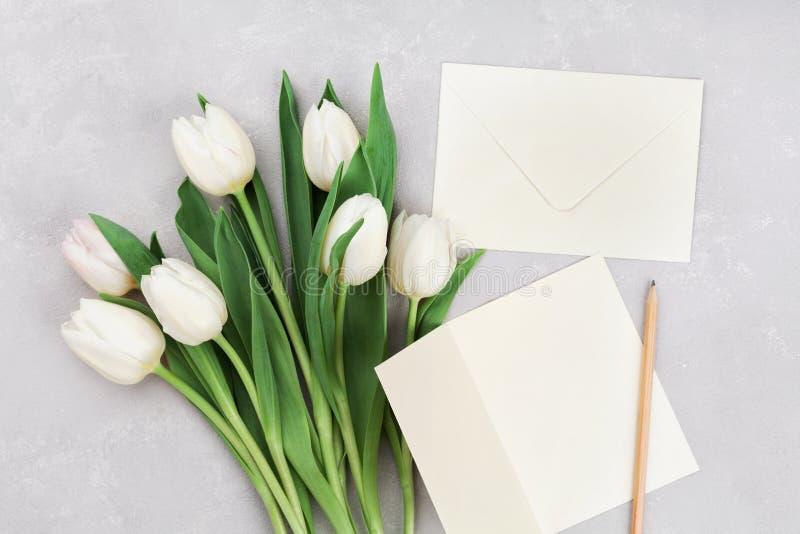 Wiosna tulipan kwitnie i papierowa karta na szarość kamienia stole od above w mieszkanie nieatutowym stylu Powitanie dla kobiet l fotografia royalty free