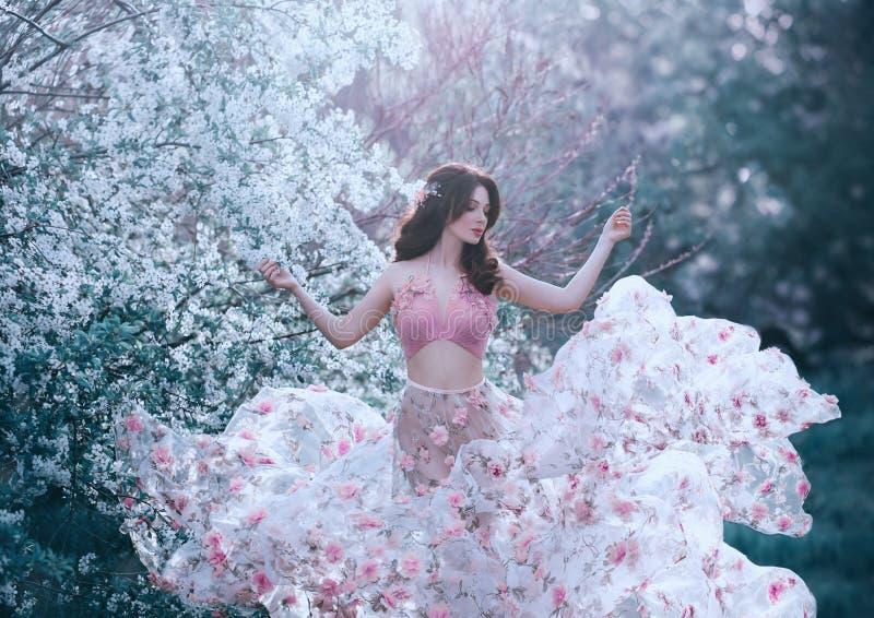 Wiosny dziewczyna z falistego włosy dancingowym tanem na tle kwiatonośni drzewa Jest ubranym różową suknię z kwiatami to fotografia stock