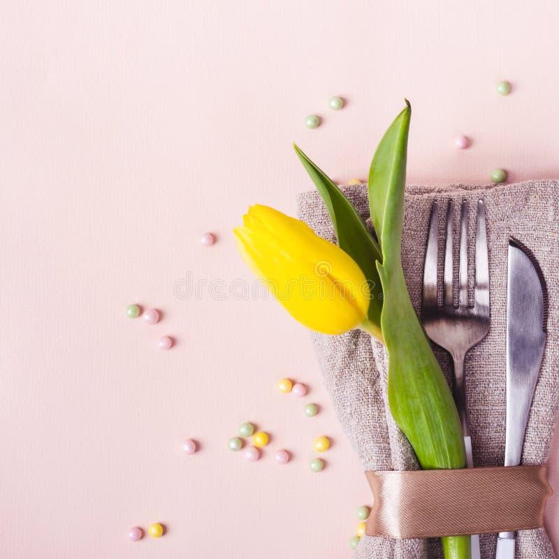Wiosny Easter stołu położenie Cutlery dekoruje z pięknym żółtym tulipanem na pastelowych menchii tle obraz stock