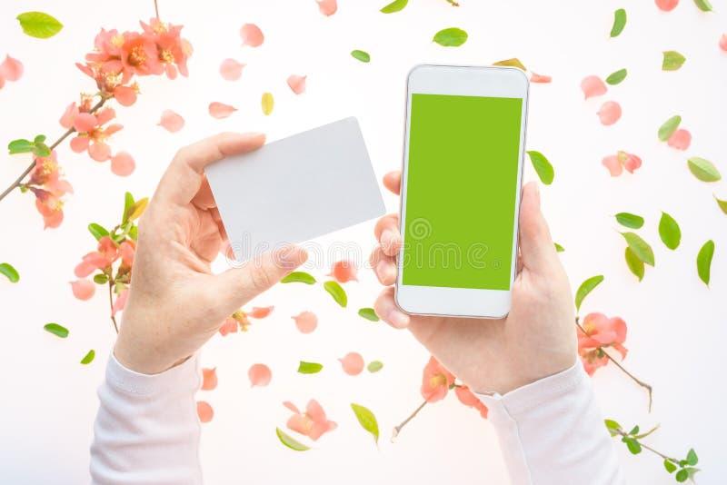 Wiosny smartphone w żeńskich rękach i wizytówka wyśmiewamy w górę zdjęcie stock