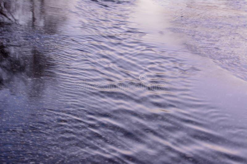 Wiosny zatoczka płynie przez asfaltowej drogi wczesna wiosna obrazy stock