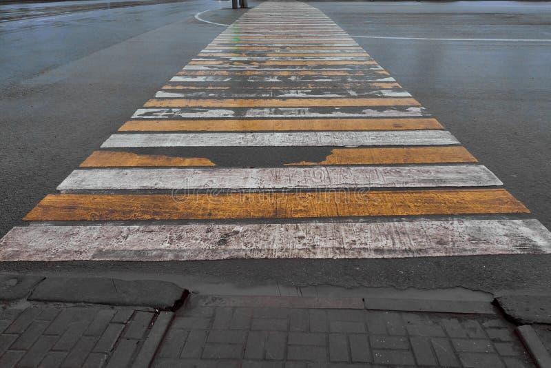 Wiped pedestrian crossing zebra on wet asphalt stock photography