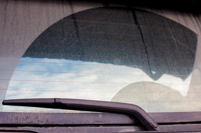 Wiper clean back car window . the dust is dirty . blue beautiful sky and cloud in shadow . stock photo