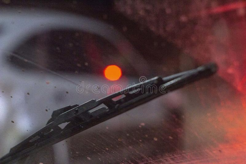 Wipers inside the car on a dirty scratched windshield, rain season, at night. the front and back backgrounds are blurred with stock images