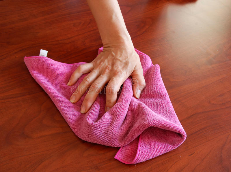 Wiping rag. Hand wiping wooden surface with pink rag royalty free stock photography