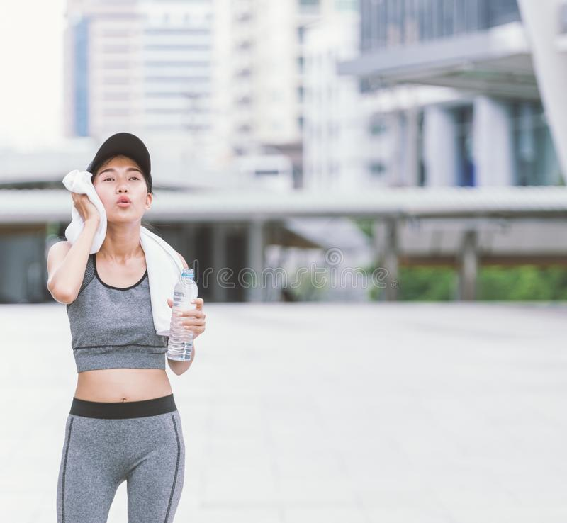 Wiping sweat Thirsty female jogger drinking fresh water after training. Young athletic woman exercising in the city park outdoors. with copy space royalty free stock photography