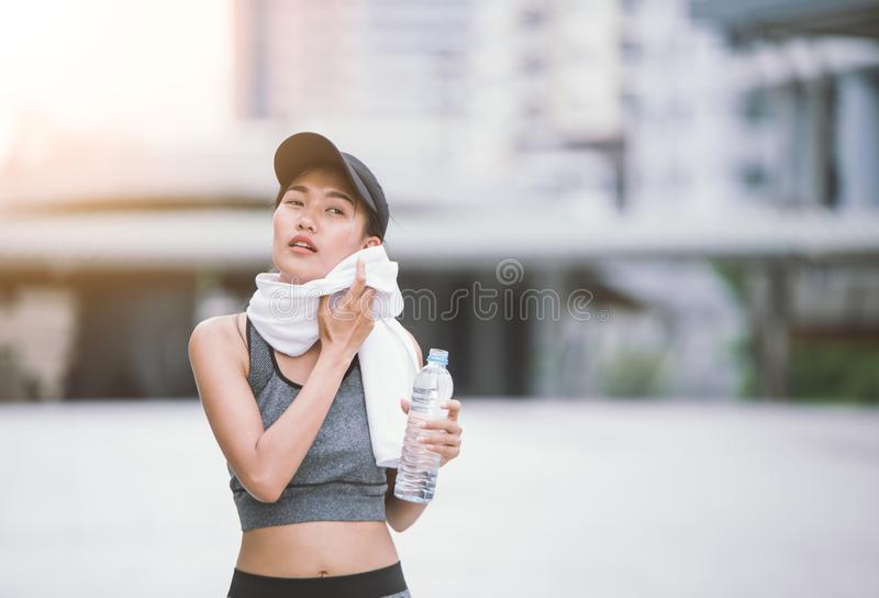 Wiping sweat Thirsty female jogger drinking fresh water. After training. Young athletic woman exercising in the city park outdoors royalty free stock image