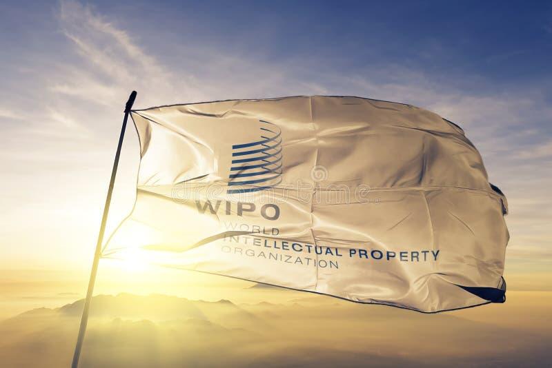 WIPO организации интеллектуальной собственности мира сигнализирует ткань ткани ткани развевая на верхнем тумане тумана восхода со бесплатная иллюстрация