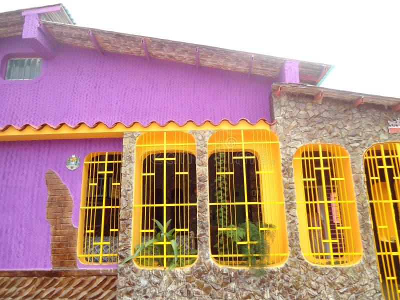 Wir haben ein typisches Dorfhaus in Venezuela mit auffallenden Farben von gelben Fenstern und von violetten und Steinwänden stockbild