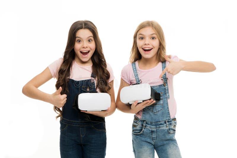 Wir mögen dieses Spiel Glückliche kleine Kinder wie Videospiele zusammen spielen Kleine Mädchen, die auf vr Kopfhörer zeigen und stockfoto