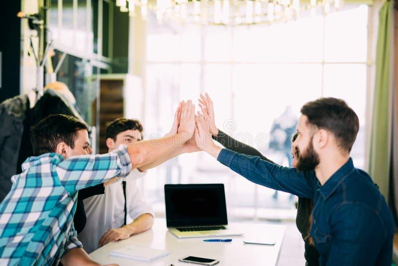 Wir sind Führer auf dem Markt Nette junge Leute, die hoch--fünf mit Lächeln beim Sitzen am Bürotisch auf BU sich geben stockbild
