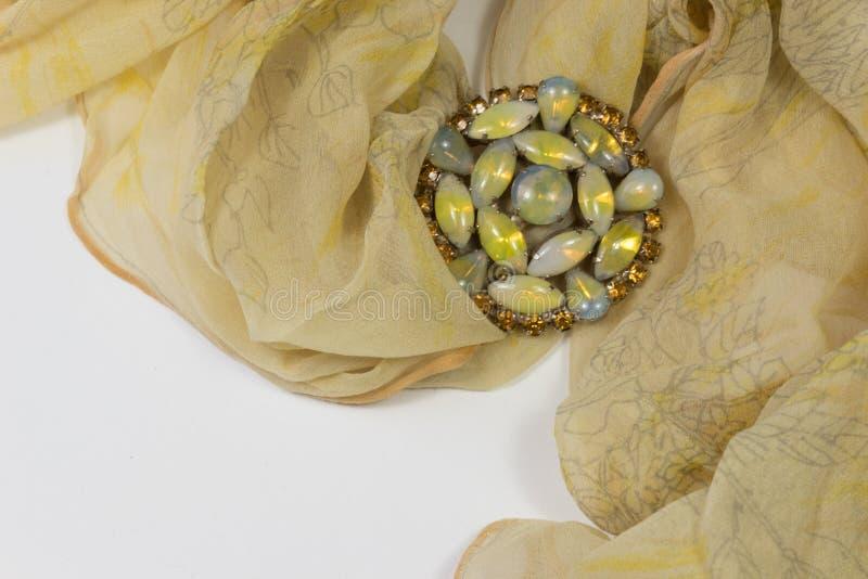 Wirbelnder bloßer gelber Schal mit Bergkristallen und Cabochonsbrosche auf Weiß stockfoto