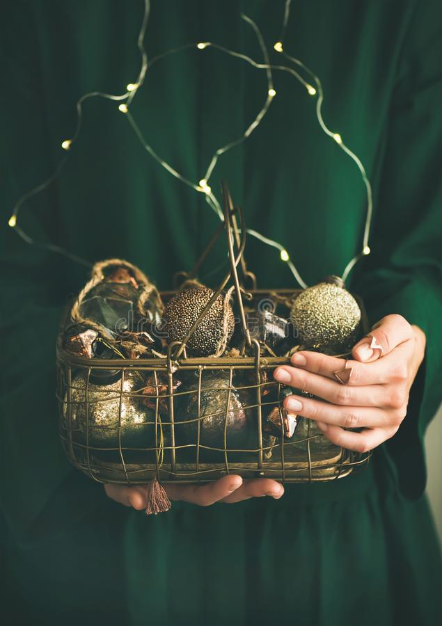 Wire basket full of Christmas or New Year decoration toys. Wire basket full of Christmas or New Year tree golden vintage decoration toys in hands of lady in royalty free stock image