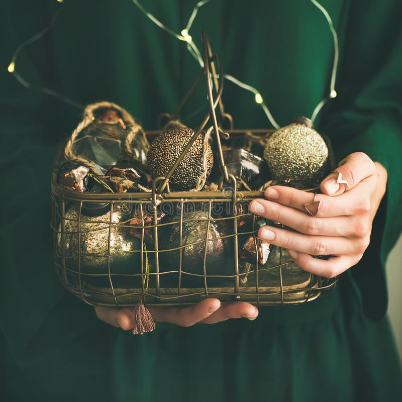 Wire basket full of Christmas decoration toys, square crop. Wire basket full of Christmas or New Year tree golden vintage decoration toys in hands of lady in stock photos