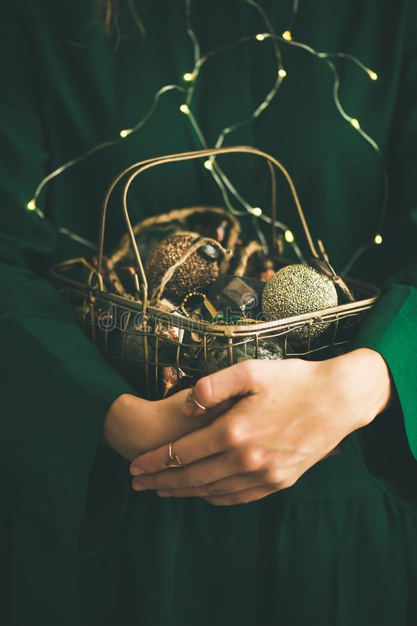 Christmas, New Year tree vintage toys in hands of woman. Wire basket full of Christmas or New Year tree vintage decoration toys in hands of woman in green stock photos