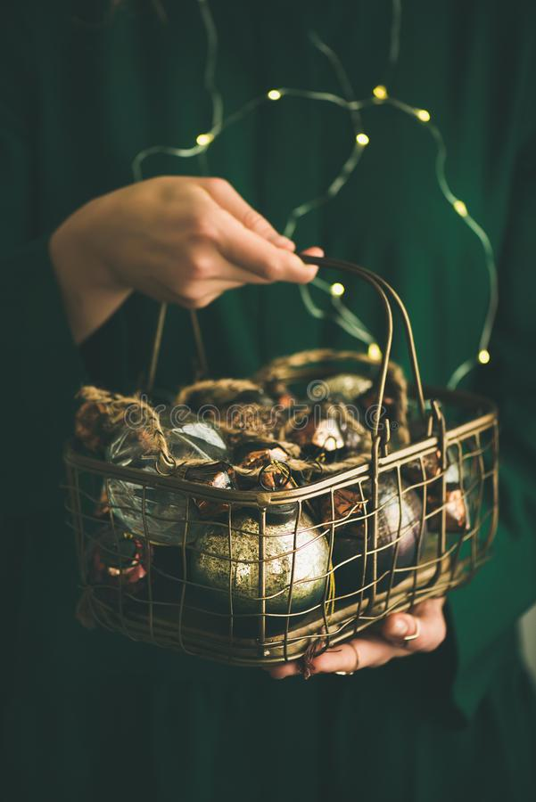 Christmas, New Year tree vintage toys in hands of woman. Wire basket full of Christmas or New Year tree vintage decoration toys in hands of woman in green stock image