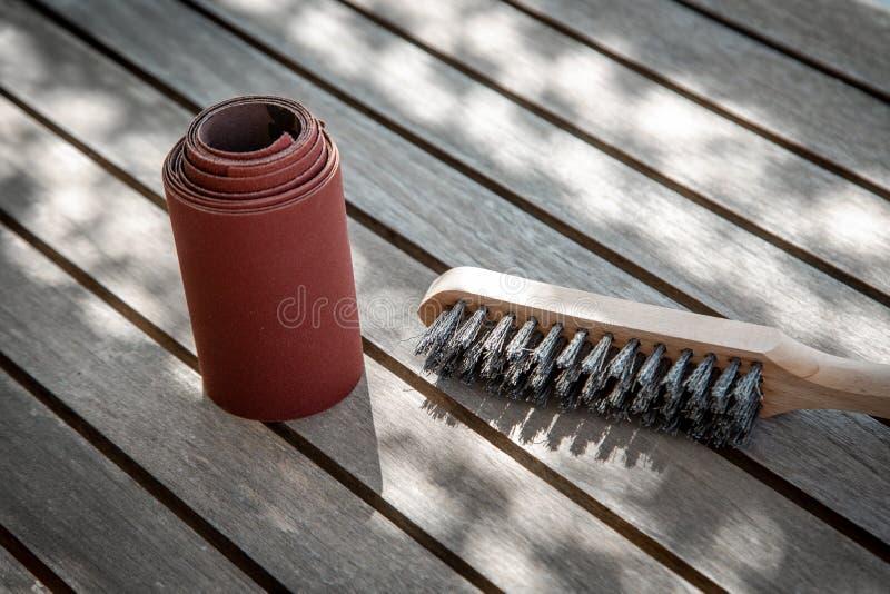Wire brush and sandpaper lying on wooden garden table before sanding stock image