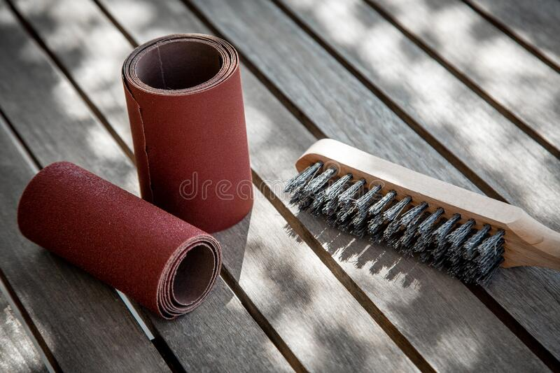 Wire brush and sandpaper lying on wooden garden table before sanding royalty free stock photography