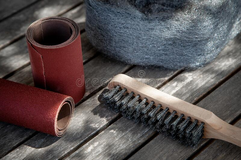 Wire brush and sandpaper lying on wooden garden table before sanding stock photos