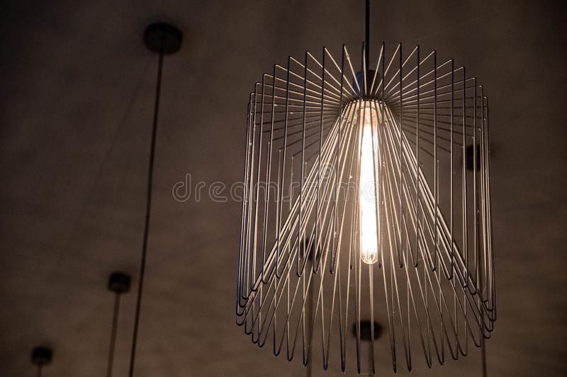 Wire chandelier closeup. Modern metal lampshade. Lamp with long glass light bulb inside. Abstract textured background. Geometric line shapes. Minimal backdrop stock illustration