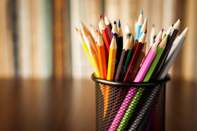 Wire desk tidy full of coloured pencils royalty free stock image