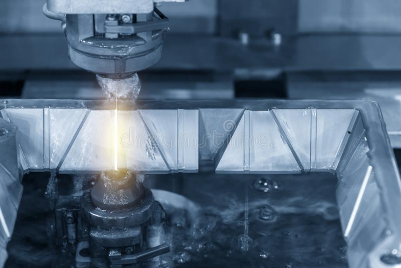 The wire EDM machine cutting the mold part . stock photo
