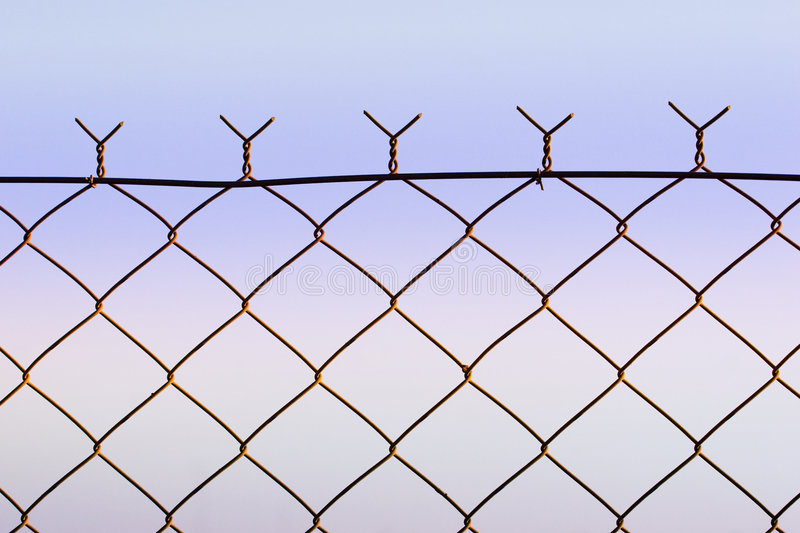 Wire fence. Top of wire fence against soft dusk sky stock images
