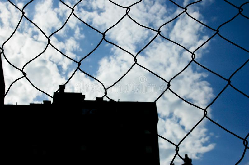 Wire fence behind blue sky with clouds stock photos