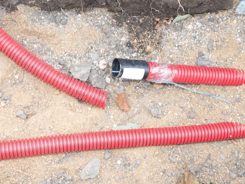 Wire in HDPE and red protectivep pipe. Lines of cables. Wire in HDPE and red protectivep pipe. Lines of metallic and fiber optic cables construction of stock photo