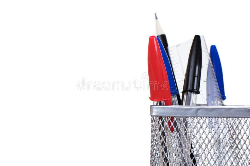 Wire mesh desk tidy with pens and a ruler royalty free stock images