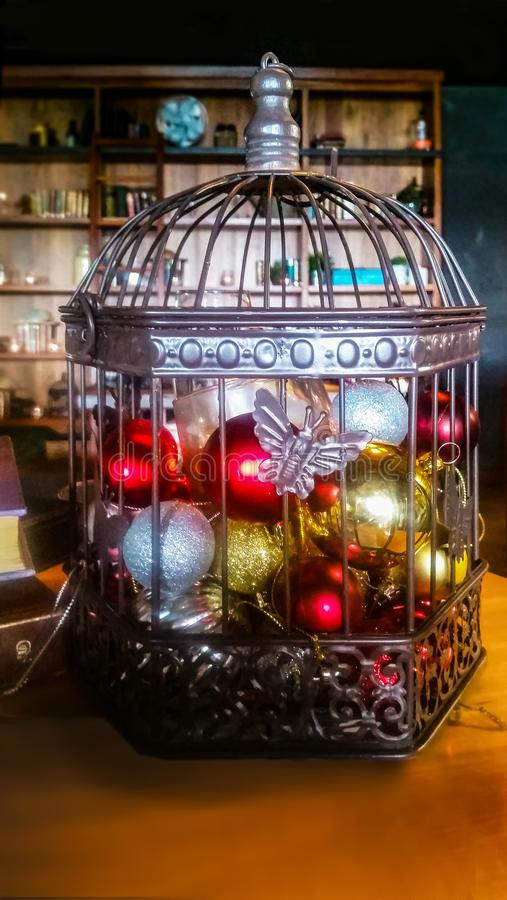 Wire and metal cage full of Christmas ornaments and lights against a dark blurry room background with shelves and laying next to b. A Wire and metal cage full of royalty free stock photography