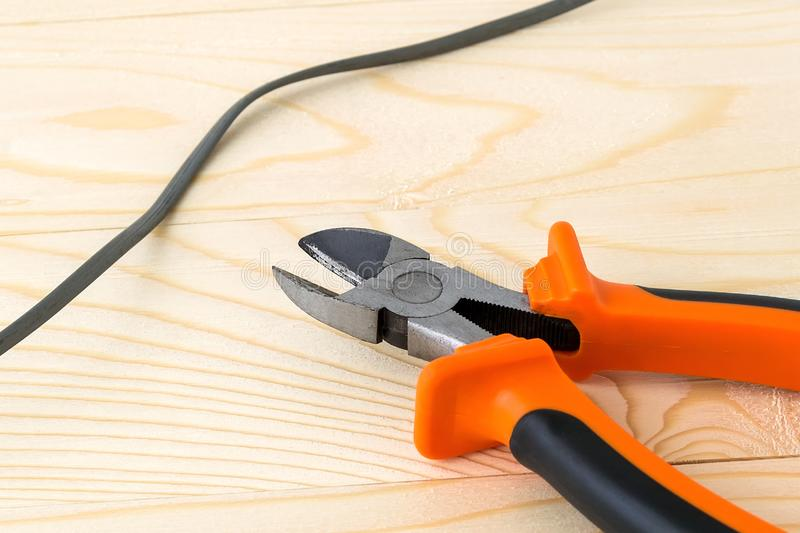 Wire and metall side cutters with orange black rubber handles on a rough wooden background. Electrician tool for repair and stock images