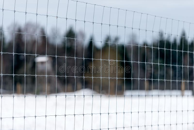 Through the wire protective fences in the distance seen in animal observation tower and forest. Focus on the foreground.  royalty free stock images
