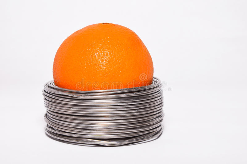 Wired orange: whole orange in coils of aluminium wire isolated o. N white background royalty free stock photo