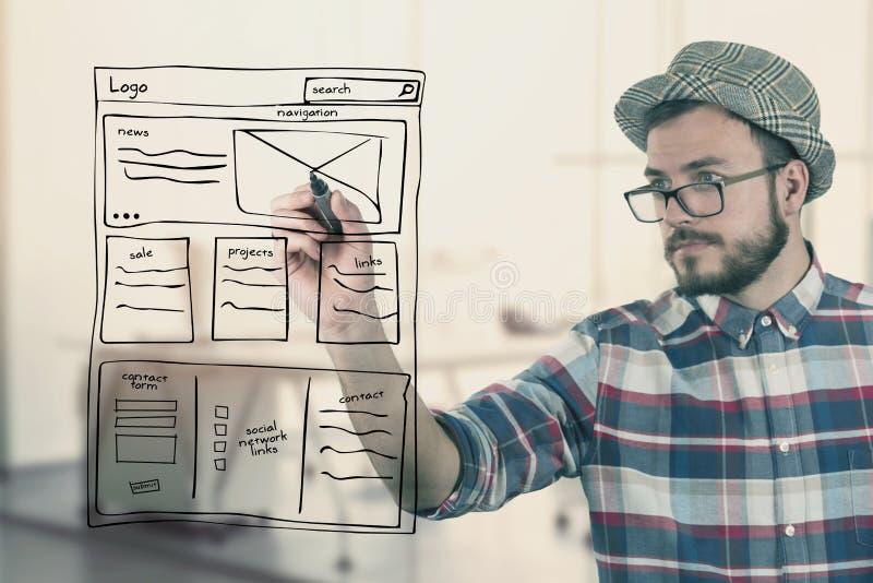 Wireframe del desarrollo del sitio web del dibujo del diseñador web en la oficina imagenes de archivo