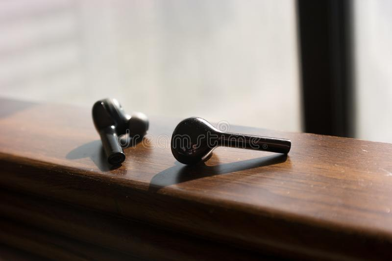 Wireless black earbuds on a wooden texture royalty free stock image