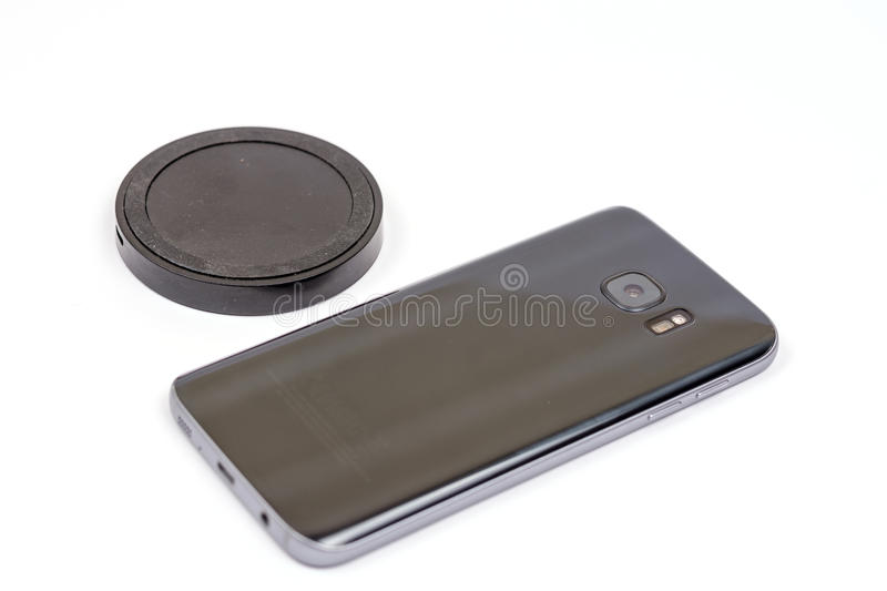 Wireless black mobile charger with mobile phone isolated over white background royalty free stock photography