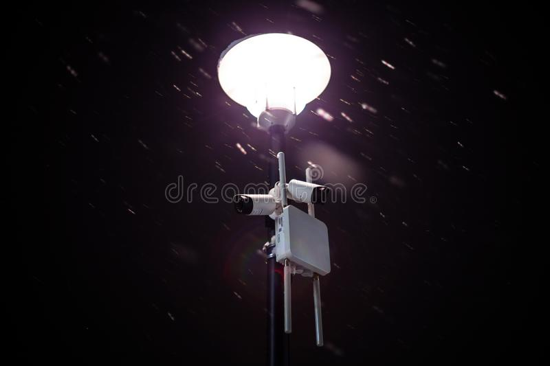 Wireless cameras on night winter lamp post with snow and selective focus.  stock photos