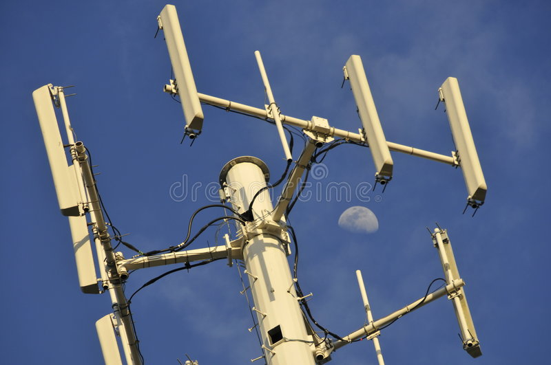 Wireless Cell Phone Antennas. Cellular Phone Tower and Antennas for Wireless Mobile Phones with Moon in Background royalty free stock photography