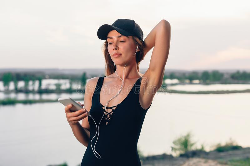 Wireless earbuds running woman on fitness workout. Active lifestyle athlete listening to smartphone music phone app with in-ear ge. Ar on beach. Weight loss stock image