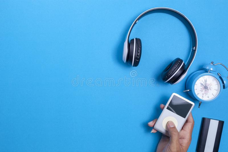 Wireless headphone and media player,blue alarm clock on blue paper background,image for media design and music website background.  stock image