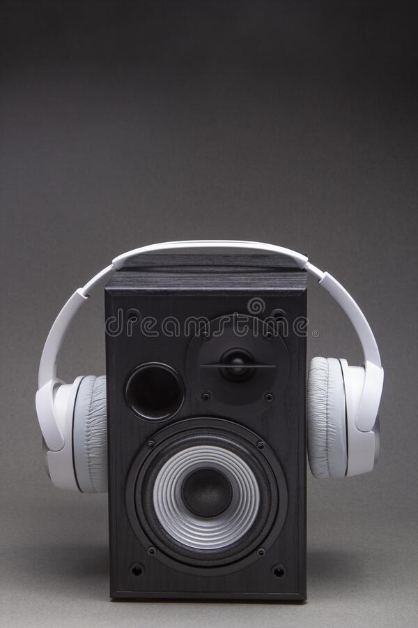 Wireless headphone on speaker isolate on grey stock photo