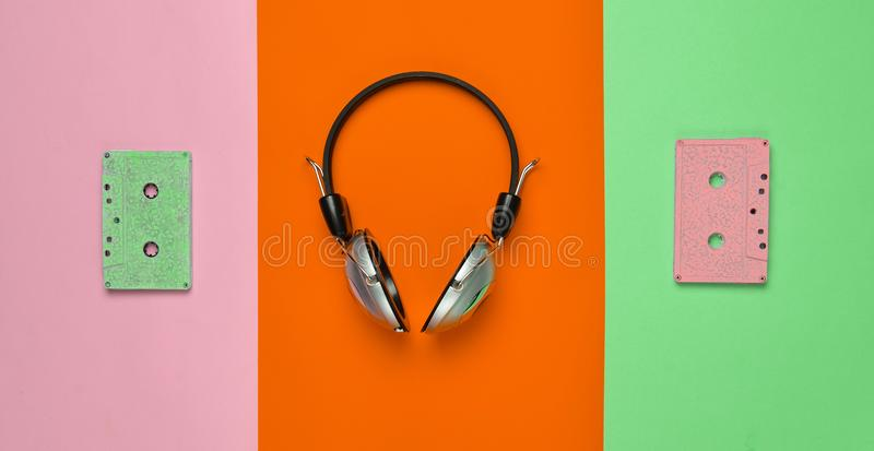 Wireless headphones and audio cassettes. On a multicolored pastel paper background. Minimal creative art. Musical retro vibrations. Top view royalty free stock photos